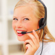 Closeup of a smiling woman wearing headset in office - Stock Photo