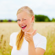 Royalty-Free Stock Photo: Happy young woman snapping fingers at a field