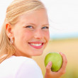 Royalty-Free Stock Photo: Cute young female holding an apple outdoors