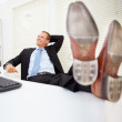 Royalty-Free Stock Photo: Handsome business man sitting in office with legs over table