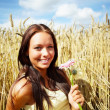 Cute young female at a crop field on a sunny day - Stock Photo