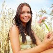 Portrait of a cute young female with flower at a crop field - Stock Photo