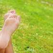 A woman&#039;s bare feet isolated on a green grass background - Foto de Stock  