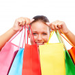 Happy young woman with colorful shopping bags on white - Стоковая фотография