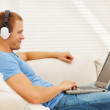 Smart young man listening to music while using a laptop - Stok fotoğraf