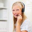 An attractive smiling woman wearing headset in office - Stock Photo