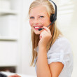 Cute smiling woman wearing headset in office - Stock Photo