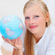 Portrait of a lovely young female holding a globe - Stock Photo