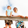 Happy father and son standing on a wooden railing outdoors - Stock Photo