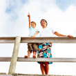 Happy father and son standing on a wooden railing outdoors, son