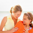 Caring mother covering her daughter with a towel at the beach - Stock Photo