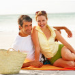 Royalty-Free Stock Photo: Cute mature couple smiling while at a beach picnic