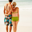 Royalty-Free Stock Photo: Beach vacation - Rear view of a couple standing on the sea shore