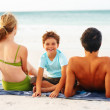 Royalty-Free Stock Photo: Adorable young boy sitting in between his parents on the beach