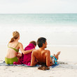 Royalty-Free Stock Photo: Happy family sitting at the beach facing the ocean