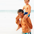 Royalty-Free Stock Photo: Happy man carrying his son on the shoulders while at the sea sho
