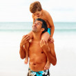Man carrying his son on the shoulders while at the beach, lookin - Stock Photo