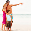 Royalty-Free Stock Photo: Happy family on their beach vacation, father pointing away