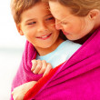 Royalty-Free Stock Photo: Caring mother embracing her son while at the beach, looking at e