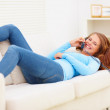 Royalty-Free Stock Photo: Happy young female lying on a sofa enjoying a phone conversation