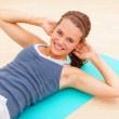 Royalty-Free Stock Photo: Pretty young female doing crunches at the gym