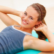 Young female doing crunches, maintaining a slim figure - Stockfoto