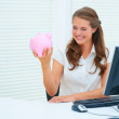Royalty-Free Stock Photo: Pretty business woman holding a piggybank while at work