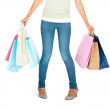 Low section of a woman with shopping bags, white background - Stock Photo