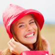 Royalty-Free Stock Photo: Closeup of a charming female wearing a red raincoat hat outdoors