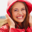 Royalty-Free Stock Photo: Closeup of a cheerful female in a red raincoat hat outdoors