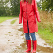 Royalty-Free Stock Photo: Young female standing in a puddle of water, wearing a red rainco