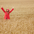 Cute female with her hands raised out in the open farm, wearing - Stock Photo