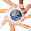 Group of with their hands together, globe in the middle - Stock Photo