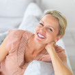 Pretty middle aged woman laughing while sitting on the couch at - Photo