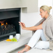 Pretty woman by a fireplace at home - Stock Photo