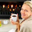 Royalty-Free Stock Photo: Happy woman having coffee by the fireplace