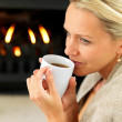 Royalty-Free Stock Photo: Woman having coffee by a fireplace