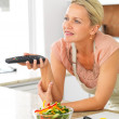 Middle aged woman with the TV remote while preparing dinner in t - Stockfoto