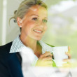Royalty-Free Stock Photo: Business woman having coffee while looking outside window