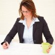 Business woman working on blue prints in the office - Stock Photo