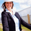 Royalty-Free Stock Photo: Happy business woman with blue prints at the construction site