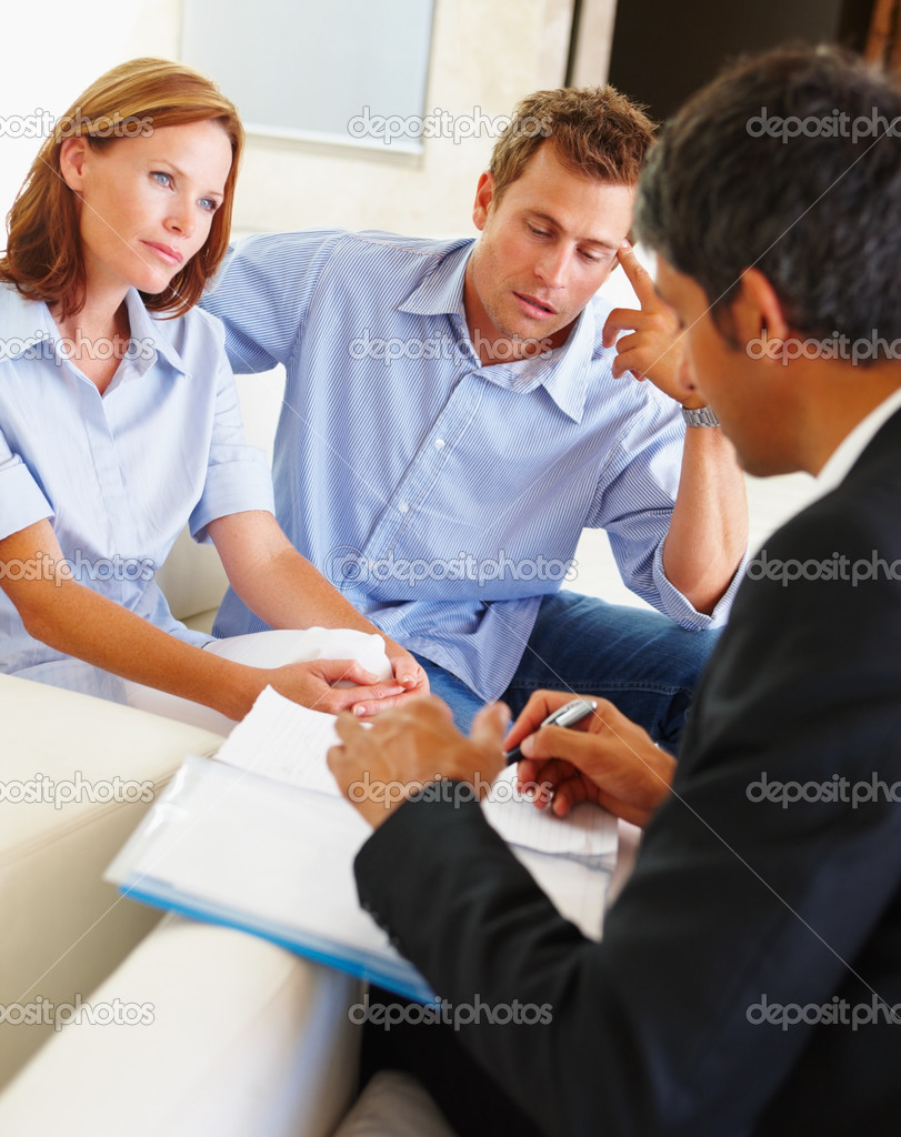 A young couple consulting a real estate agent at home — Stock Photo #3330336