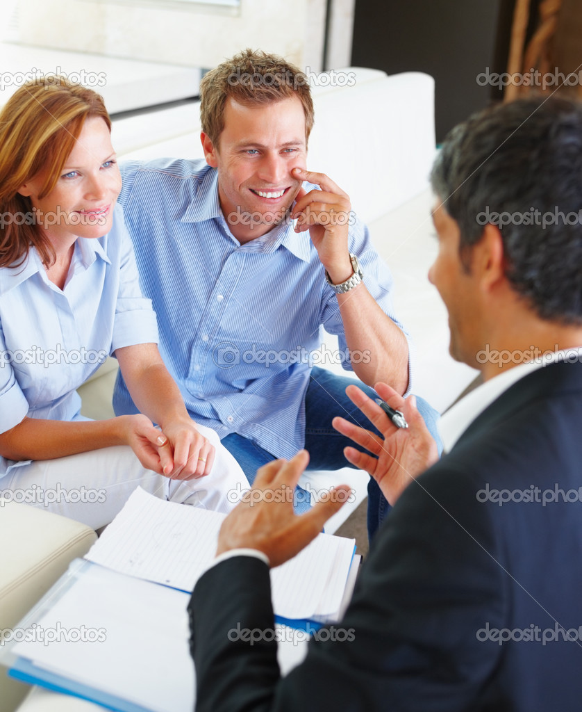 A young couple consulting a financial planner at home — Stock Photo #3330337