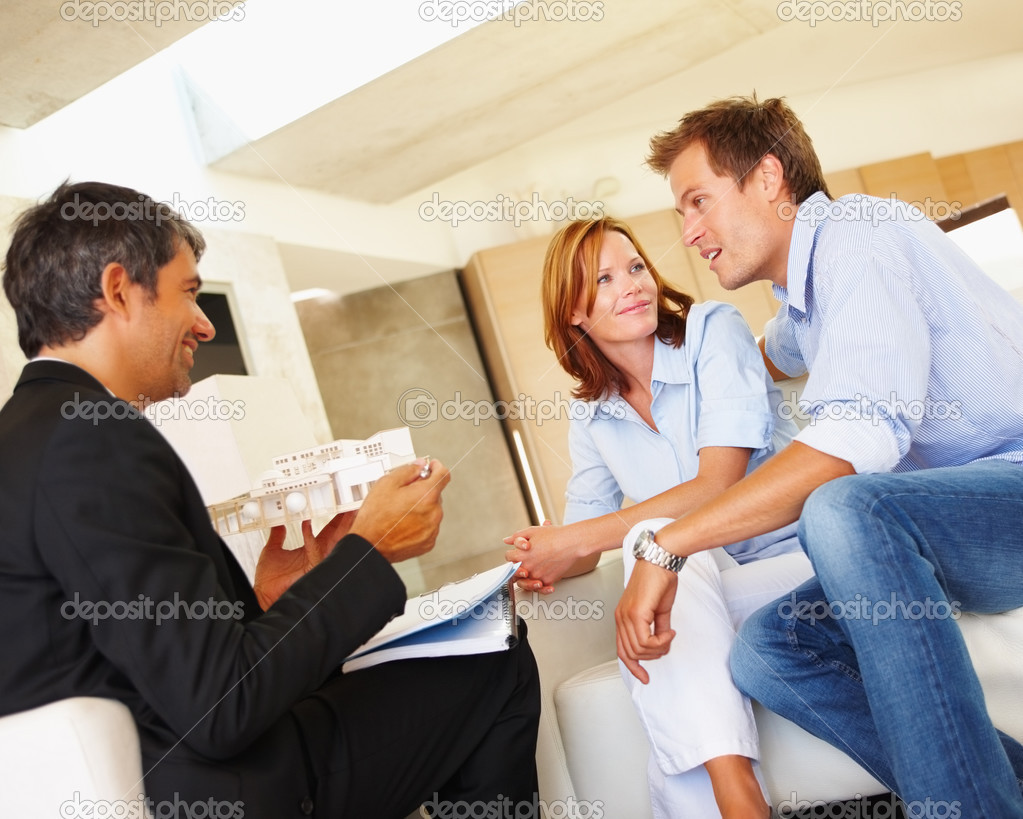 Young couple getting help from a real estate agent — Stock Photo #3330348
