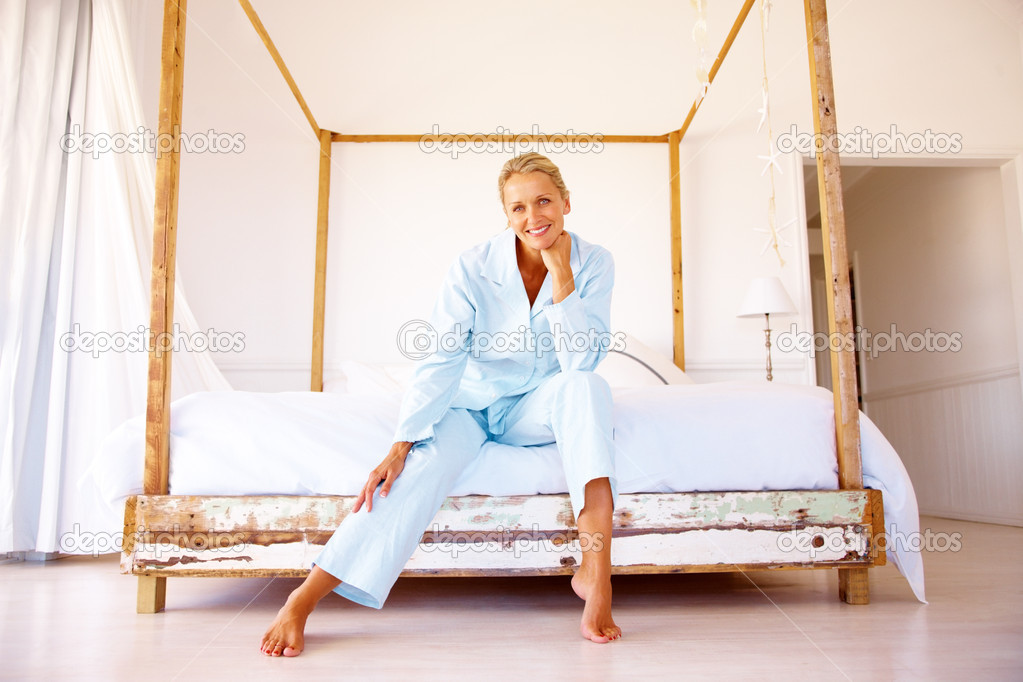 Portrait of a smiling pretty blond sitting on a bed in her apartment  Stock Photo #3330943