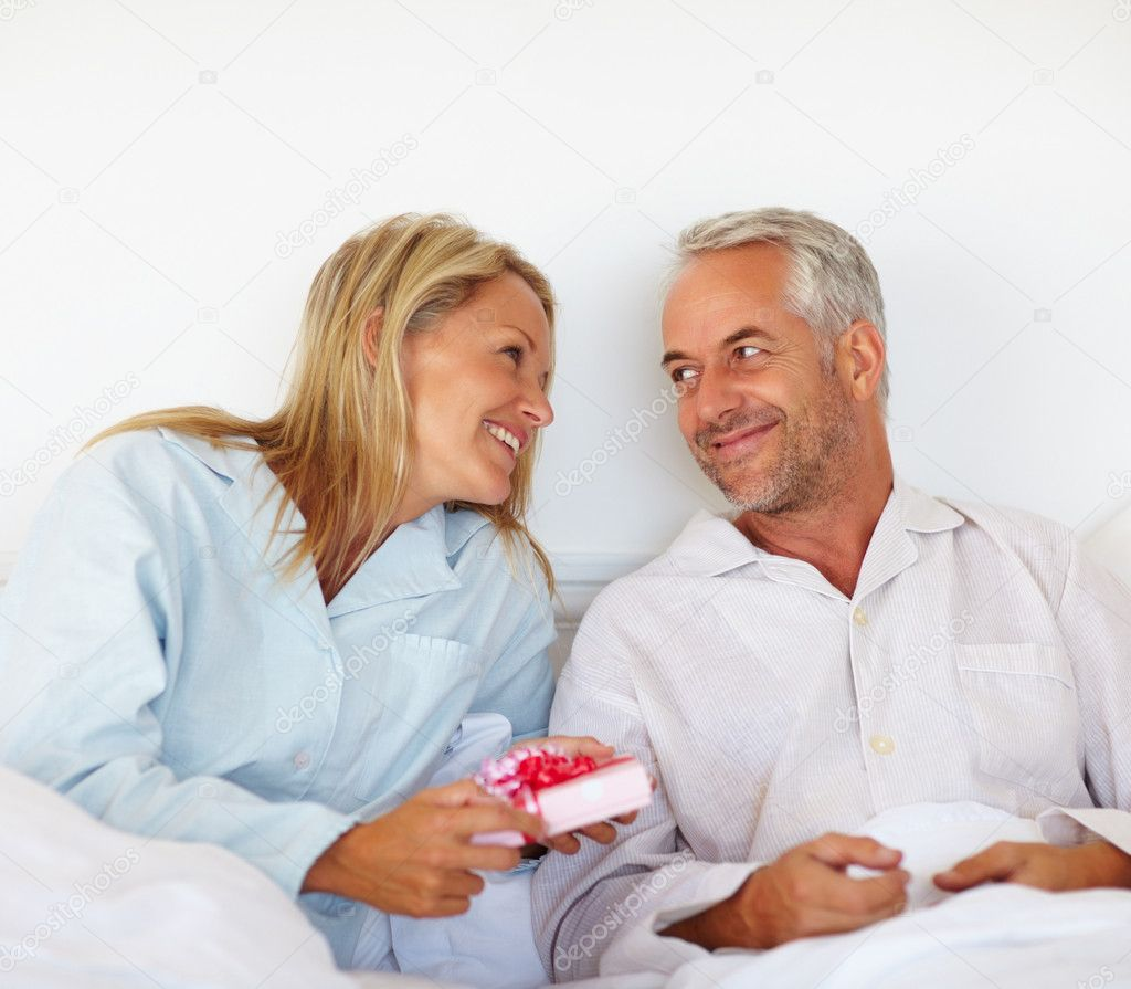 Senior couple in the bed exchanging gifts — Photo #3330992