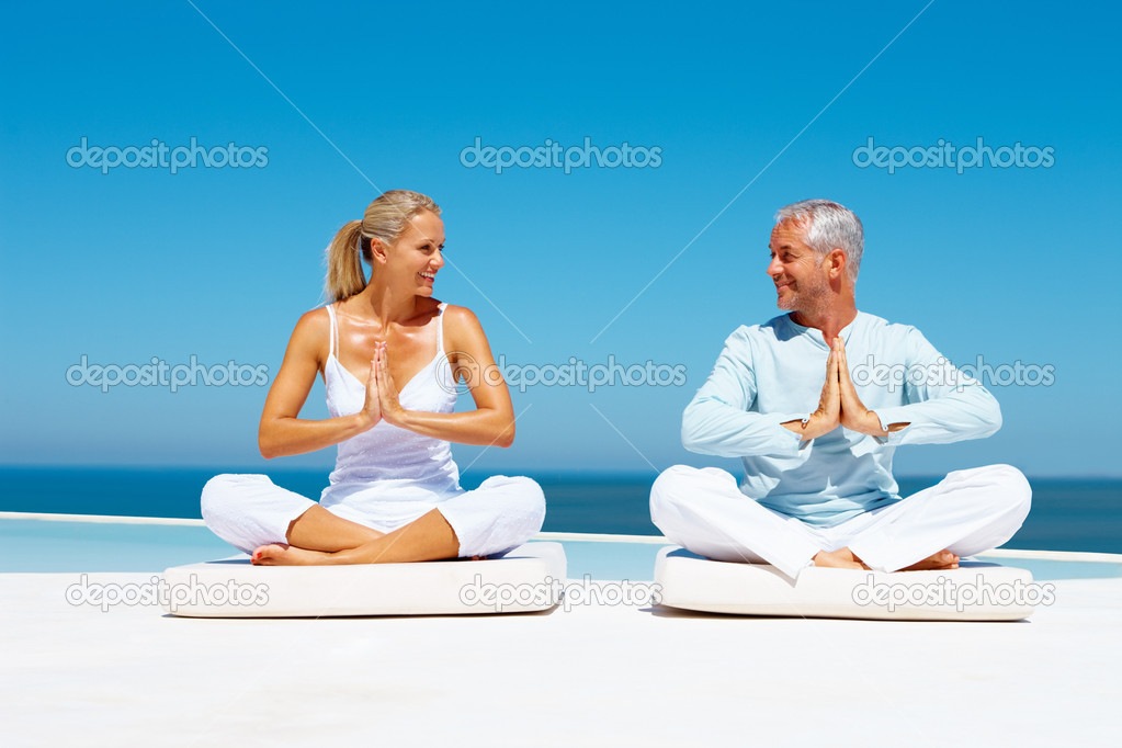 A fit senior couple meditating at the sea shore — Stock Photo #3331539