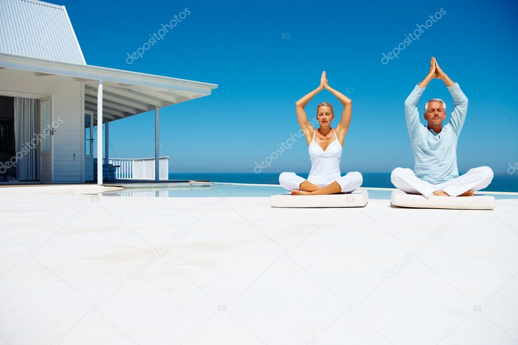 Happy couple on the beach practicing yoga with a cottage in the background — Stockfoto #3331543
