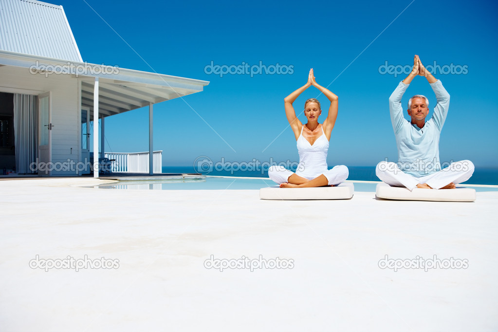 Happy couple on the beach practicing yoga with a cottage in the background — Lizenzfreies Foto #3331543