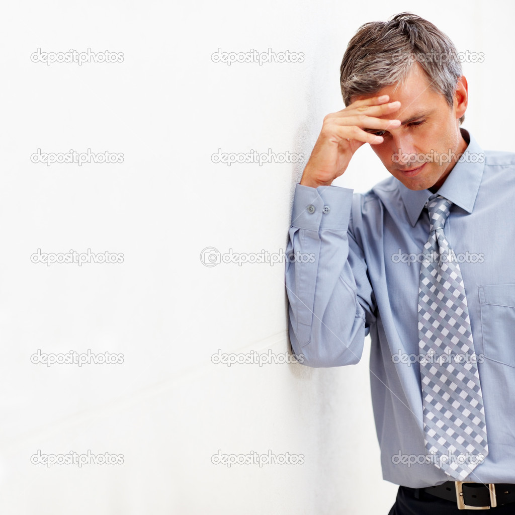 Mature business man with a head ache against a white wall — Stock Photo #3332118